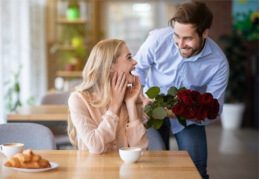 A Man Surprising A Happy Woman With A Bouquet of Red Roses. How To Create A Relationship of Lasting Love.